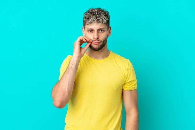 Junger gutaussehender kaukasischer mann isoliert auf blauem hintergrund, der ein zeichen der stille zeigt