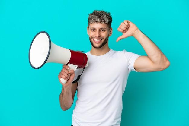 Junger gutaussehender kaukasischer mann isoliert auf blauem hintergrund mit einem megaphon und stolz und selbstzufrieden