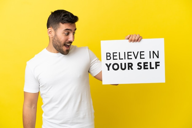 Junger gutaussehender kaukasischer mann isoliert auf gelbem hintergrund, der ein plakat mit dem text believe in your self hält