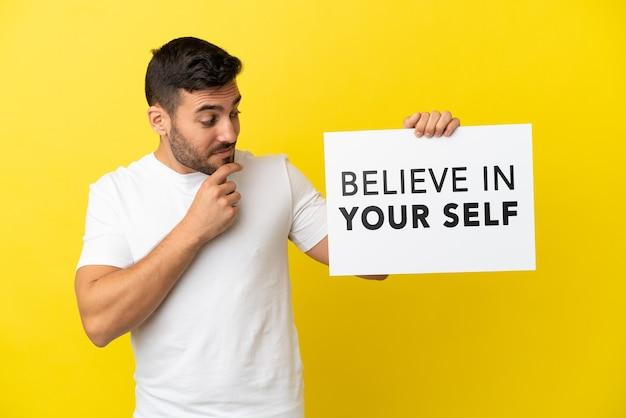 Junger gutaussehender kaukasischer mann isoliert auf gelbem hintergrund, der ein plakat mit dem text