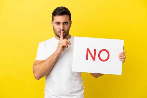 Junger gutaussehender kaukasischer mann isoliert auf gelbem hintergrund, der ein plakat mit dem text hält, keine stillegeste zu tun