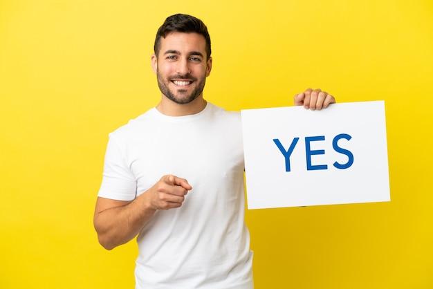 Junger gutaussehender kaukasischer mann isoliert auf gelbem hintergrund, der ein plakat mit dem text ja hält und darauf zeigt