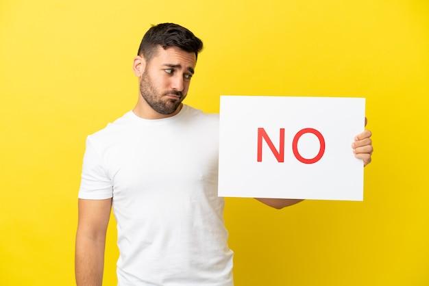 Junger gutaussehender kaukasischer mann isoliert auf gelbem hintergrund, der ein plakat mit dem text nein hält