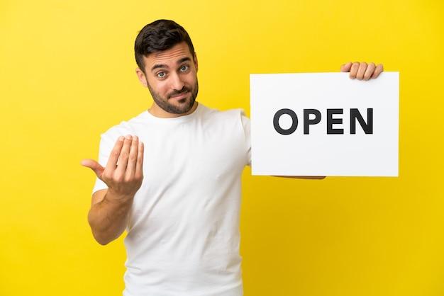 Junger gutaussehender kaukasischer mann isoliert auf gelbem hintergrund, der ein plakat mit dem text open hält und kommende geste macht