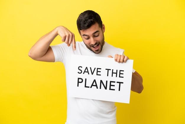 Junger gutaussehender kaukasischer mann isoliert auf gelbem hintergrund, der ein plakat mit dem text save the planet hält und darauf zeigt