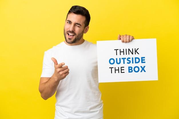Junger gutaussehender kaukasischer mann isoliert auf gelbem hintergrund, der ein plakat mit dem text think outside the box hält und nach vorne zeigt
