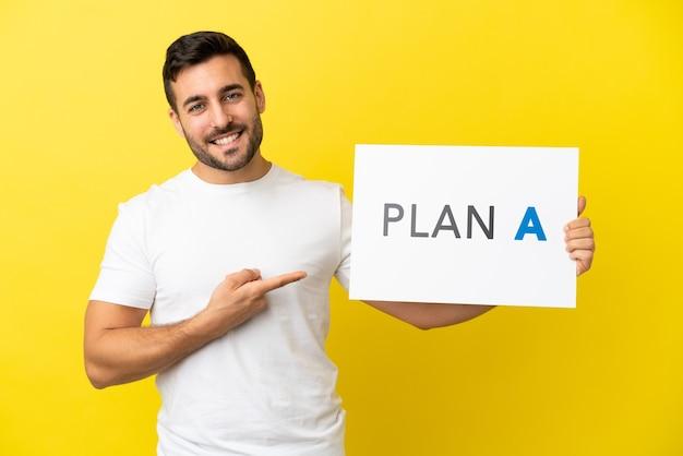 Junger gutaussehender kaukasischer mann isoliert auf gelbem hintergrund, der ein plakat mit der nachricht plan a hält und darauf zeigt