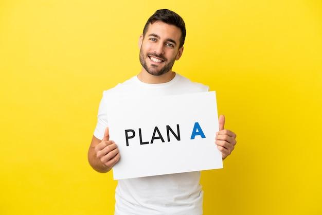 Junger gutaussehender kaukasischer mann isoliert auf gelbem hintergrund, der ein plakat mit der nachricht plan a hält