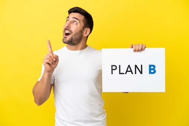 Junger gutaussehender kaukasischer mann isoliert auf gelbem hintergrund, der ein plakat mit der nachricht plan b hält und denkt
