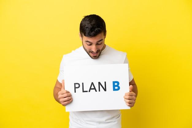 Junger gutaussehender kaukasischer mann isoliert auf gelbem hintergrund, der ein plakat mit der nachricht plan b hält