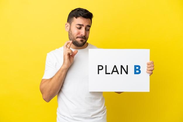 Junger gutaussehender kaukasischer mann isoliert auf gelbem hintergrund, der ein plakat mit der nachricht plan b mit den fingern überquert hält