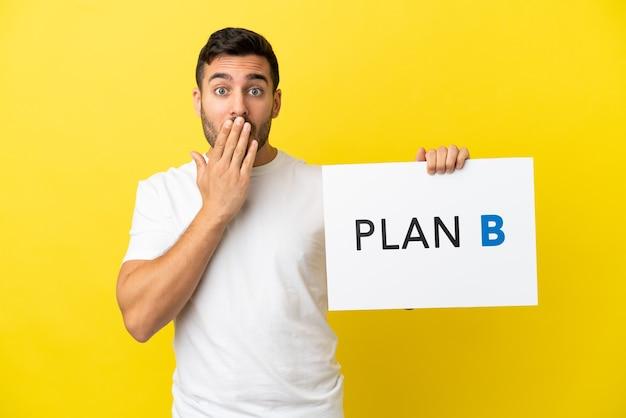 Junger gutaussehender kaukasischer mann isoliert auf gelbem hintergrund, der ein plakat mit der nachricht plan b mit überraschtem ausdruck hält