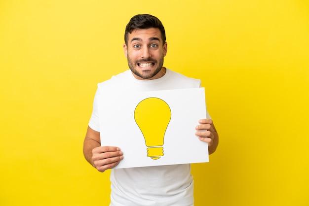 Junger gutaussehender kaukasischer mann isoliert auf gelbem hintergrund, der ein plakat mit glühbirnensymbol mit glücklichem ausdruck hält