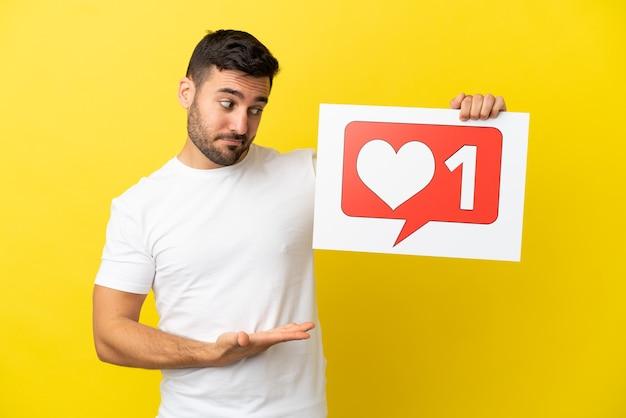 Junger gutaussehender kaukasischer mann isoliert auf gelbem hintergrund, der ein plakat mit like-symbol hält und darauf zeigt