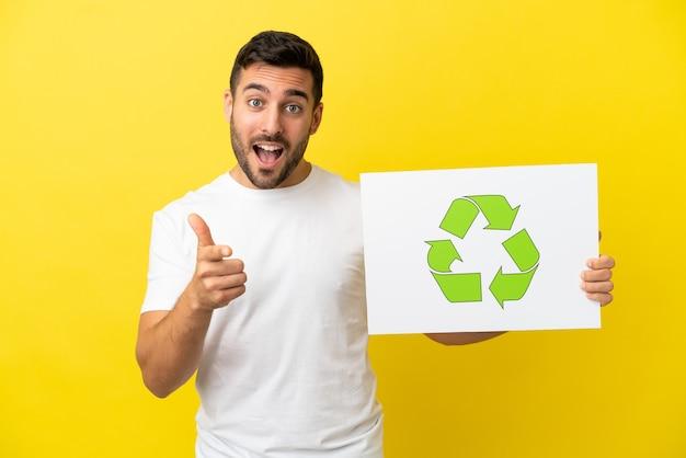 Junger gutaussehender kaukasischer mann isoliert auf gelbem hintergrund, der ein plakat mit recycling-symbol hält und auf die vorderseite zeigt