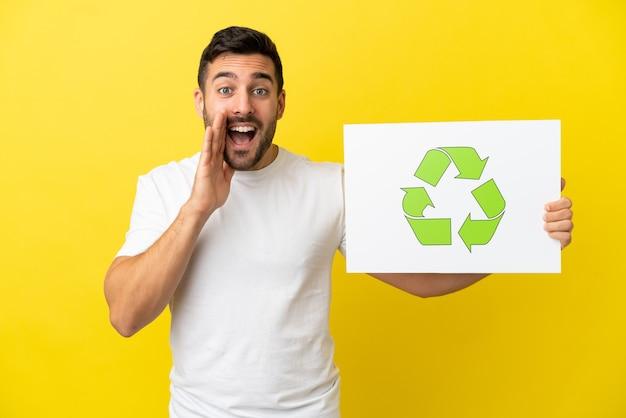 Junger gutaussehender kaukasischer mann isoliert auf gelbem hintergrund, der ein plakat mit recycling-symbol hält und schreit