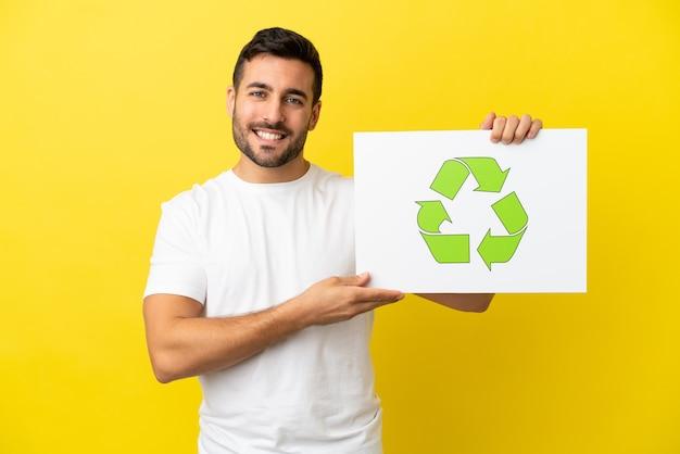 Junger gutaussehender kaukasischer mann isoliert auf gelbem hintergrund, der ein plakat mit recycling-symbol mit glücklichem ausdruck hält