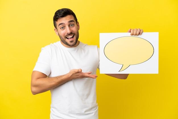 Junger gutaussehender kaukasischer mann isoliert auf gelbem hintergrund, der ein plakat mit sprechblasensymbol hält und darauf zeigt