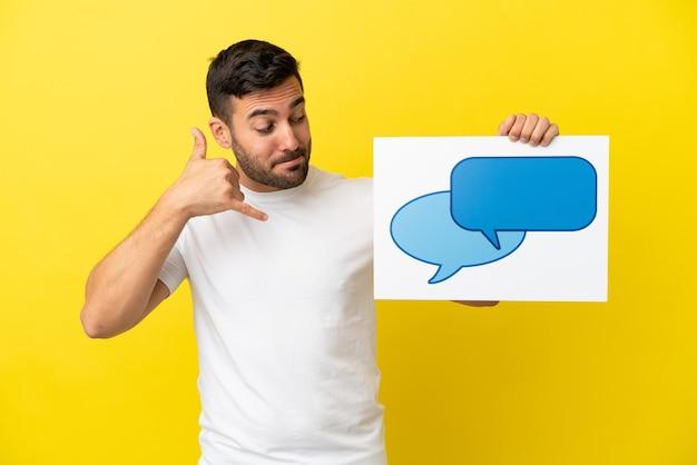 Junger gutaussehender kaukasischer mann isoliert auf gelbem hintergrund, der ein plakat mit sprechblasensymbol hält und telefongeste macht