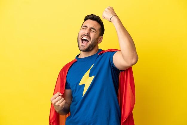 Junger gutaussehender kaukasischer mann isoliert auf gelbem hintergrund im superheldenkostüm und feiert einen sieg