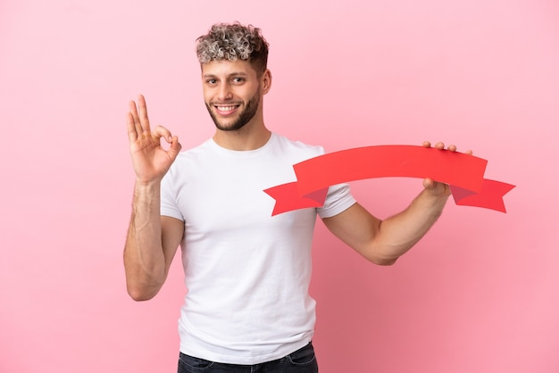 Junger gutaussehender kaukasischer mann isoliert auf rosa hintergrund, der ein leeres plakat hält und ok-zeichen macht
