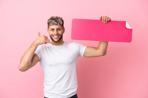 Junger gutaussehender kaukasischer mann isoliert auf rosa hintergrund, der ein leeres plakat hält und telefongeste macht