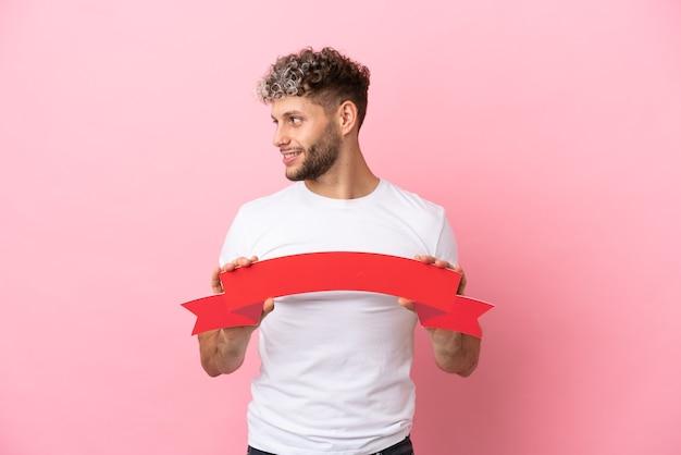 Junger gutaussehender kaukasischer mann isoliert auf rosa hintergrund, der ein leeres plakat hält und zur seite schaut