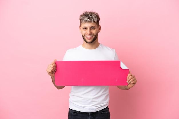 Junger gutaussehender kaukasischer mann isoliert auf rosa hintergrund, der ein leeres plakat hält