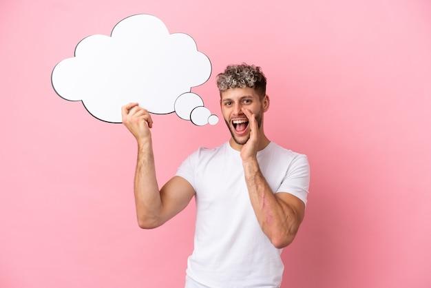 Junger gutaussehender kaukasischer mann isoliert auf rosa hintergrund, der eine denkende sprechblase hält und schreit