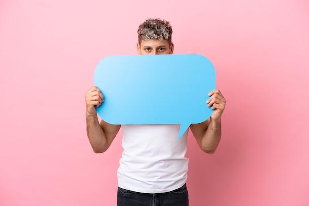 Junger gutaussehender kaukasischer mann, isoliert auf rosa hintergrund, der eine leere sprechblase hält, die sich dahinter versteckt, versteckt sich dahinter