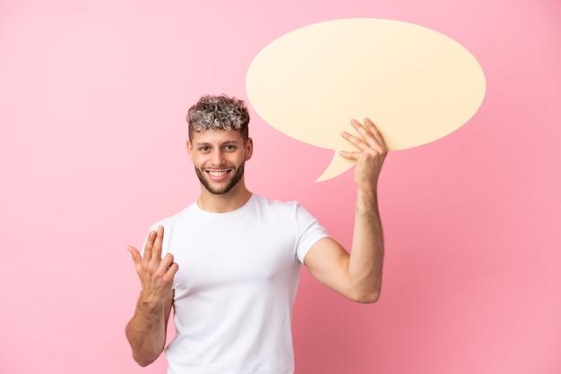 Junger gutaussehender kaukasischer mann isoliert auf rosa hintergrund, der eine leere sprechblase hält und eine kommende geste macht