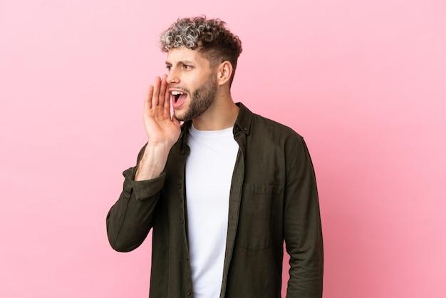 Junger gutaussehender kaukasischer mann isoliert auf rosa hintergrund, der mit weit geöffnetem mund zur seite schreit