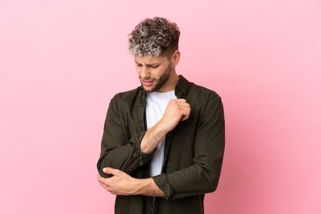 Junger gutaussehender kaukasischer mann isoliert auf rosa hintergrund mit schmerzen im ellenbogen