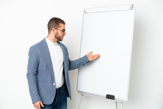 Junger gutaussehender kaukasischer mann isoliert auf weißem hintergrund, der eine präsentation auf dem whiteboard hält