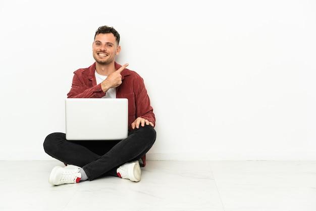 Junger gutaussehender kaukasischer mann sitzt auf dem boden mit laptop, der auf die seite zeigt, um ein produkt zu präsentieren