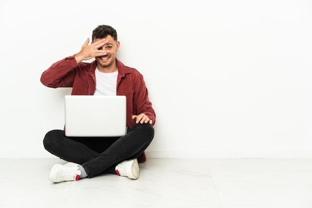 Junger gutaussehender kaukasischer mann sitzt auf dem boden mit laptop, der die augen mit den händen bedeckt und lächelt