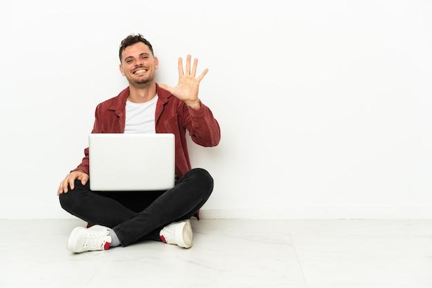 Junger gutaussehender kaukasischer mann sitzt auf dem boden mit laptop, der fünf mit den fingern zählt