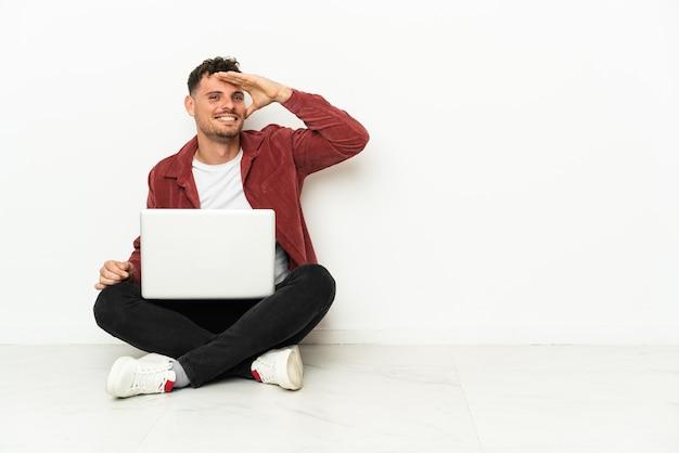 Junger gutaussehender kaukasischer mann sitzt auf dem boden mit laptop, der mit der hand weit weg schaut, um etwas zu suchen