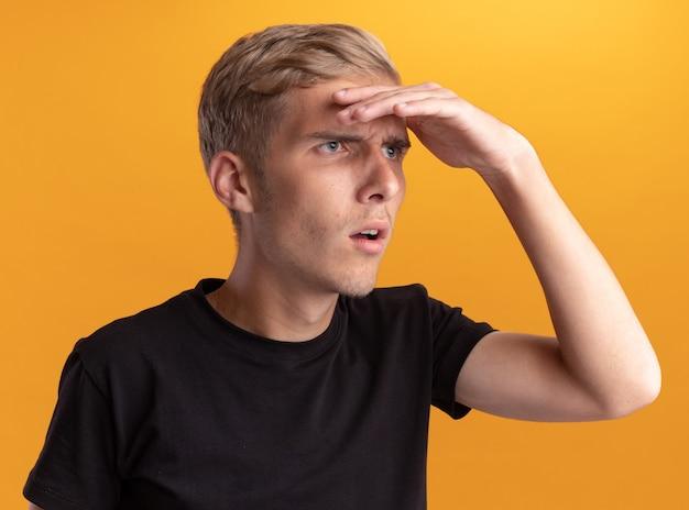 Junger gutaussehender kerl, der ein schwarzes hemd trägt und in die ferne schaut, mit der hand, die auf gelber wand isoliert ist?