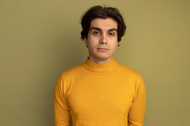 Junger gutaussehender kerl, der in die kamera schaut und einen gelben rollkragenpullover trägt, der auf einer olivgrünen wand isoliert ist?