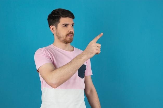Junger gutaussehender kerl, der mit dem finger auf die luft zeigt und auf blau wegschaut.