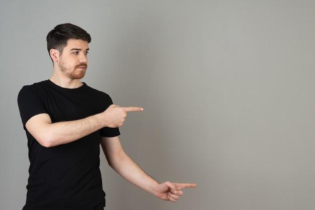 Junger gutaussehender kerl, der mit dem finger auf ein grau zeigt.