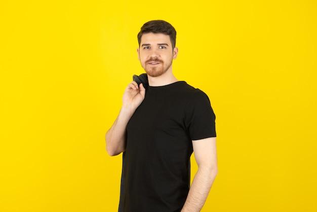 Junger gutaussehender kerl in einem beiläufigen tragen, das die kamera auf einem gelb betrachtet.