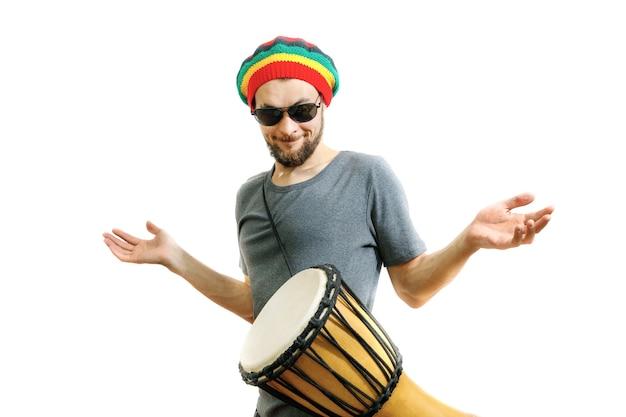 Junger gutaussehender kerl lernt, das djembe-trommelinstrument auf weißem hintergrund zu spielen.