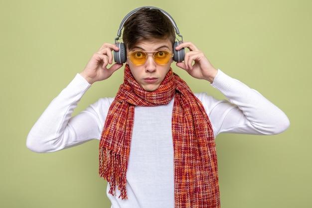 Junger gutaussehender kerl mit schal mit brille und kopfhörern isoliert auf olivgrüner wand