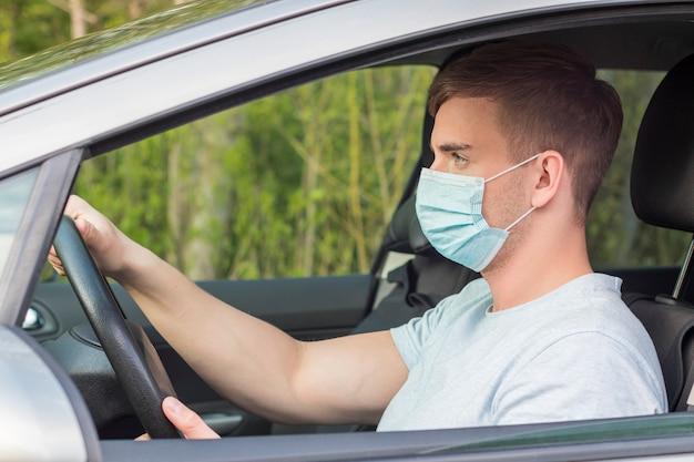 Junger gutaussehender konzentrierter kerl, fahrer, ernster mann, der ein auto in der medizinischen schutzmaske auf seinem gesicht fährt, autorad hält und straßenfahrt genießt. coronavirus, pandemie, virus-covid-19-konzept