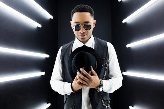 Junger gutaussehender lächelnder hipster schwarzer mann im retro-vintage-stil anzug tanzen hip-hop im disco-nachtclub, spaß haben