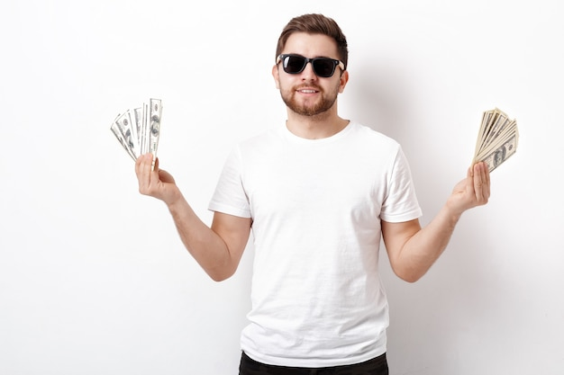 Junger gutaussehender lächelnder mann mit bart in einem weißen hemd und einer sonnenbrille, die viele hundert-dollar-scheine hält. geld