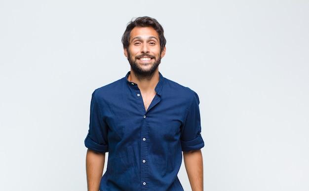 Junger gutaussehender lateinamerikanischer mann, der glücklich und doof mit einem breiten, lustigen, verrückten lächeln und weit geöffneten augen schaut