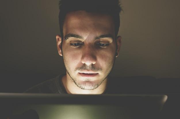 Junger gutaussehender mann am laptop mit lichtreflexion vom bildschirm zum gesicht - technologie, internet und personenkonzept